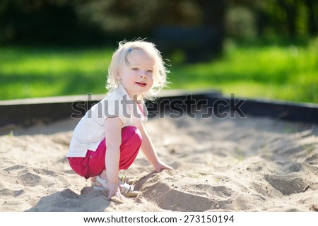 Adorable little girl playing in a sandbox on hot and sunny summer day - stock photo
