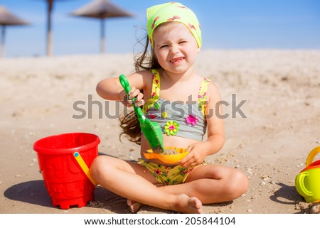 Adorable little girl playing in the sand on the beach - stock photo
