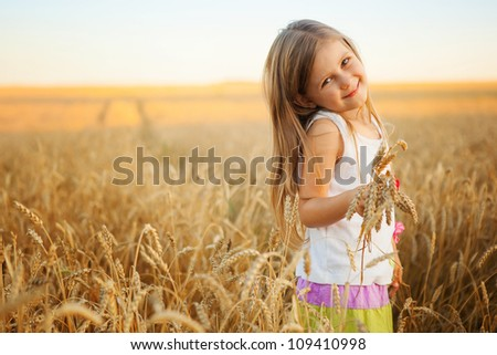 Adorable little girl playing in the wheat field on a warm summer day - stock photo