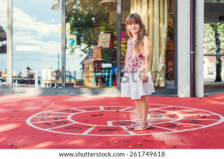 Adorable little girl playing on a schoolyard - stock photo