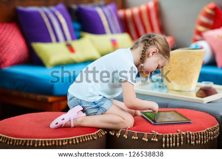 Adorable little girl playing on a tablet device - stock photo