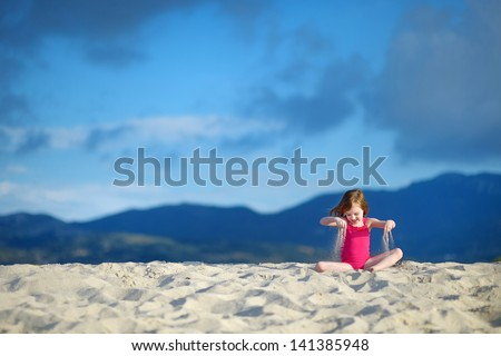 Adorable little girl playing on beautiful sandy beach