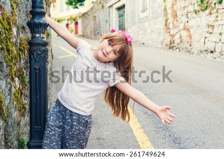Adorable little girl playing outdoors on a nice summer day - stock photo
