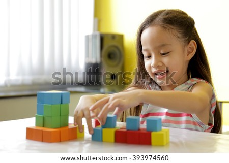 Adorable little girl playing toy blocks in a bright room - selective focused