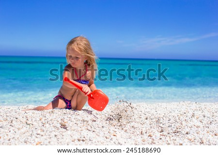 Adorable little girl playing with beach toys during summer vacation