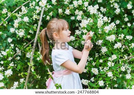 Adorable little girl playing with jasmin tree in a park on a nice spring day - stock photo