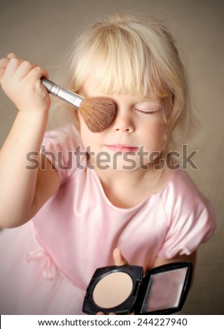 Adorable little girl playing with mommy's make up - stock photo