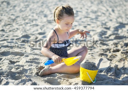 Adorable little girl playing with sand at the beach in summer