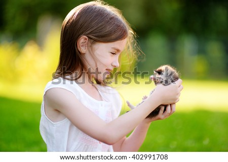 Adorable little girl playing with small kitten at warm and sunny summer day