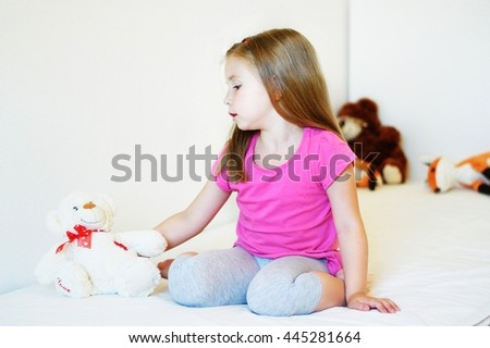 Adorable little girl playing with teddy bear - stock photo