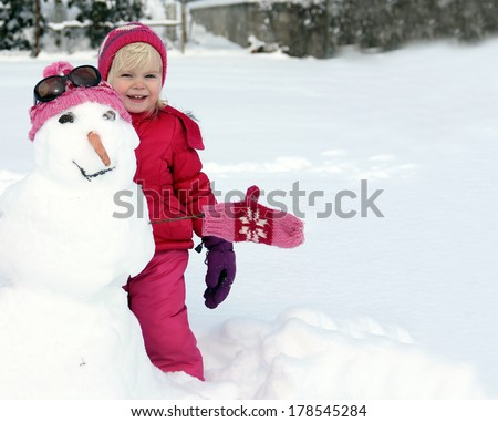Adorable little girl playing with the snowman - stock photo