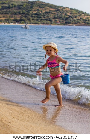 Adorable Little Girl Playing with toys at sandy beach. Summer vacation.