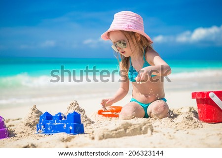 Adorable little girl playing with toys on beach vacation - stock photo