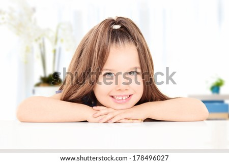 Adorable little girl posing indoors, seated at a table