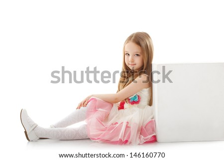 Adorable little girl posing leaning on cube