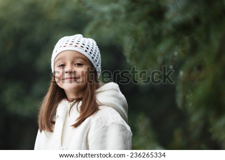 Adorable little girl posing near the branch of tree and smiling in to a camera. Wearing winter coat and hat. Lovely young girl in the winter outdoors.