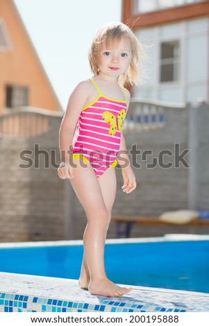 Adorable little girl posing near water pool