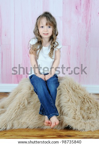 adorable little girl posing on brown fur rug with a pink backdrop - stock photo