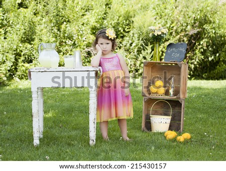 Adorable little girl pouting that she has no customers at her lemonade stand.