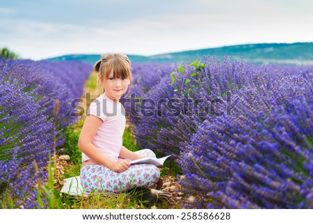 Adorable little girl reading a book in a lavender field on a nice sunny evening - stock photo