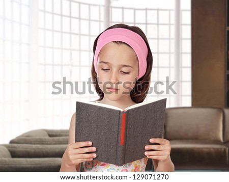 Adorable little girl reading a book in her home - stock photo