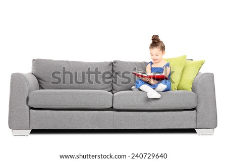 Adorable little girl reading a book on sofa isolated on white background - stock photo