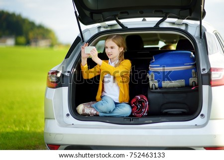Adorable little girl ready to go on vacations with her parents. Kid playing with her phone in a car. Traveling by car with kids.