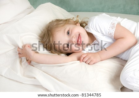 Adorable little girl rest in bed tongue hanging out - stock photo