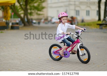 Adorable little girl riding a bike in a city