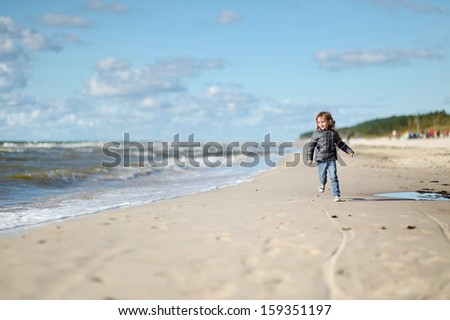 Adorable little girl running and laughing on the beach