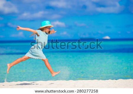 Adorable little girl running on tropical white beach - stock photo