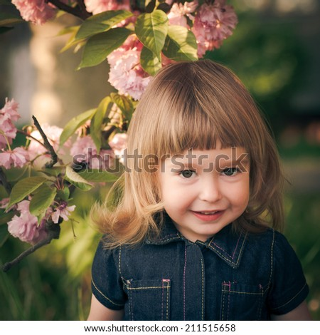 Adorable little girl's portrait in the garden, sakura blossom - stock photo