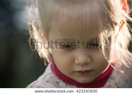 Adorable little girl sad face. Sad look. Eyes down
