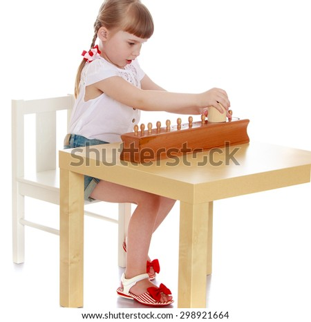 Adorable little girl sitting at table and studying Montessori materials , Montessori kindergarten - stock photo