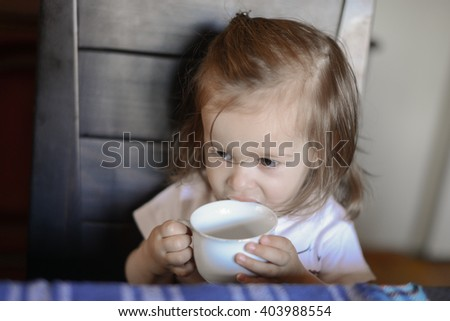 adorable little girl sitting at the dining room table drinking from a white cup - stock photo