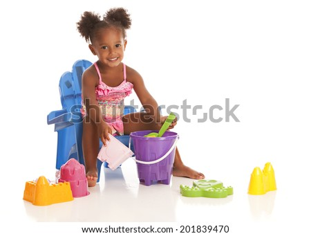 Adorable little girl sitting in a beach chair and playing with sand toys.  Isolated on white with room for your text. - stock photo