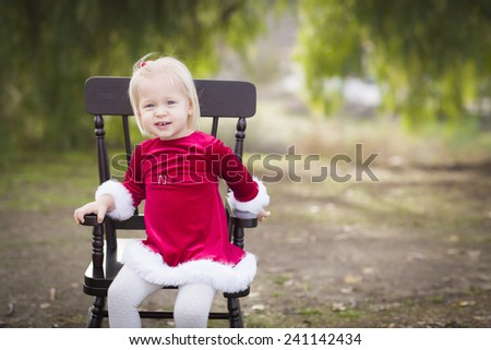 Adorable Little Girl Sitting in Her Rocking Chair Outside. - stock photo