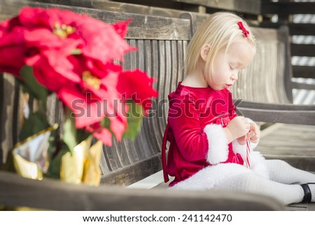 Adorable Little Girl Sitting On A Bench with Her Candy Cane Outside. - stock photo