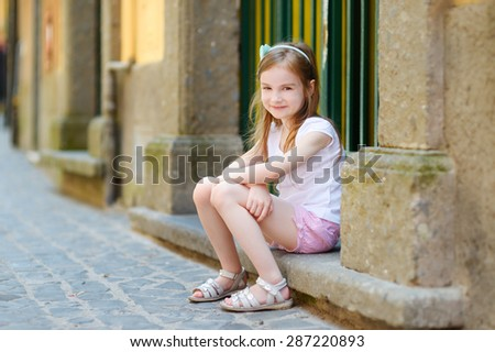 Adorable little girl sitting on a doorstep on warm and sunny summer day in typical italian town