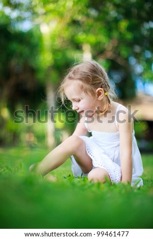 Adorable little girl sitting on a grass