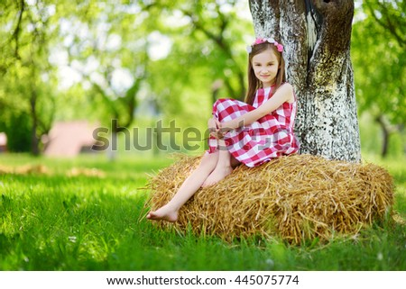 Adorable little girl sitting on a haystack in apple tree garden on warm and sunny summer day - stock photo