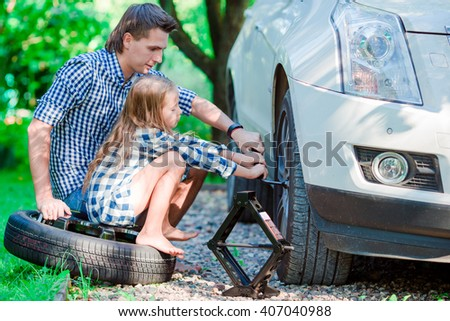 Adorable little girl sitting on a tire and helping father to change a car wheel outdoors on beautiful summer day - stock photo