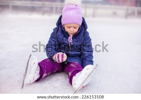 Adorable little girl sitting on ice with skates after the fall - stock photo