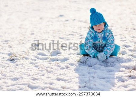 Adorable little girl sitting on the snowy ground outdoors on a winter's day - stock photo