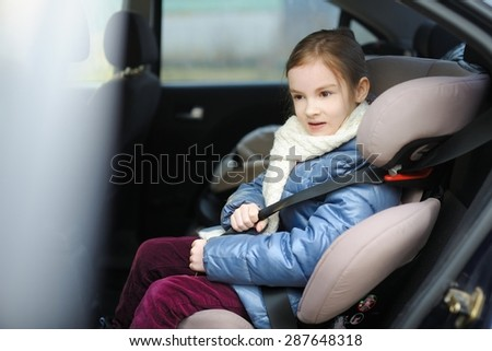 Adorable little girl sitting safely in a car seat