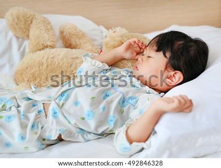 Adorable little girl sleeping in the bed with her toy