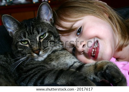 Adorable little girl snuggling with her pet cat.