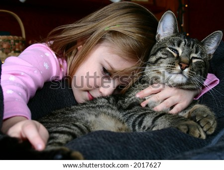 Adorable little girl snuggling with her pet cat. - stock photo