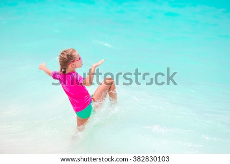 Adorable little girl splashing in tropical shallow water during summer vacation