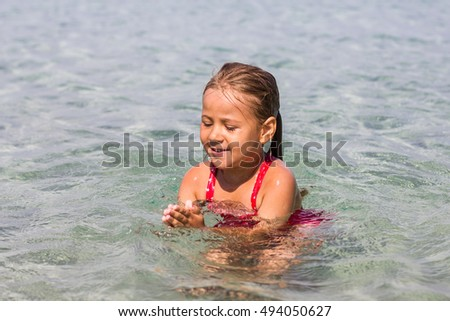 Adorable Little girl swimming in the sea. Summer Vacation